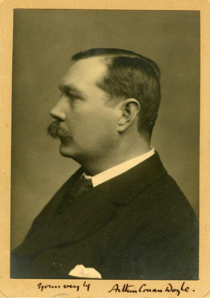 A black and white photograph of an older Conan Doyle