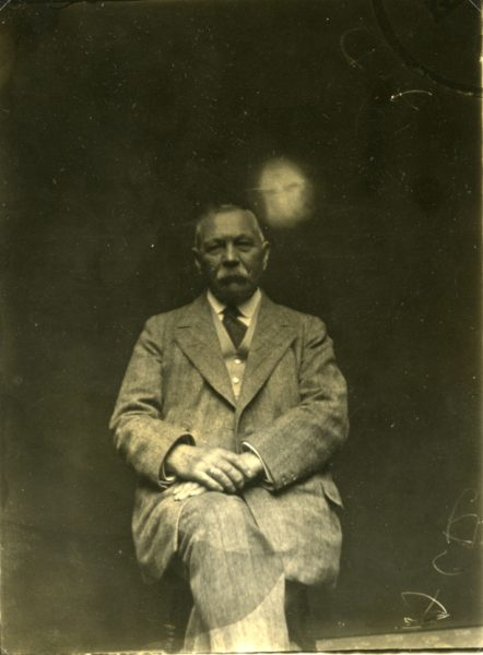 A portrait of Conan Doyle with a blurred white face over his shoulder