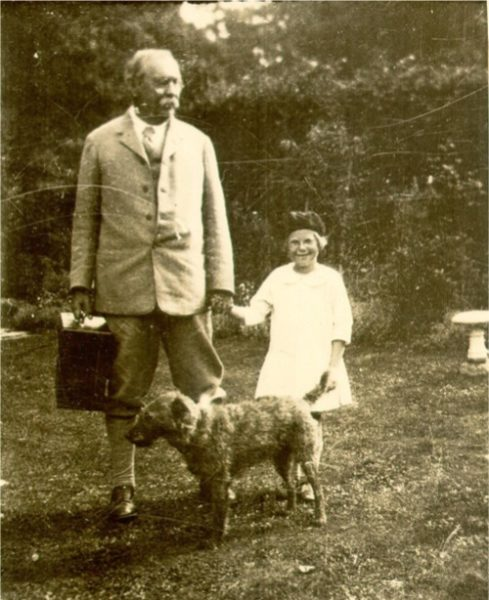Man and child holding hands. Also a dog