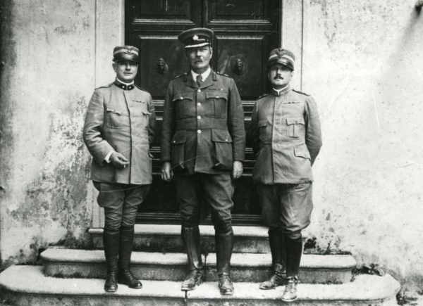 Three men in military uniform standing on steps