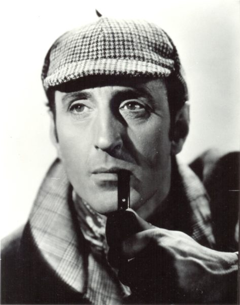 Black and white image of man with pipe and wearing a deerstalker hat