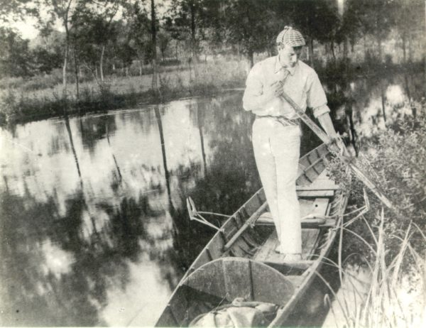 Man standing in a boat with steer and wearing a deerstalker hat