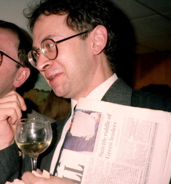 Photograph of man holding a wine glass and a newspaper