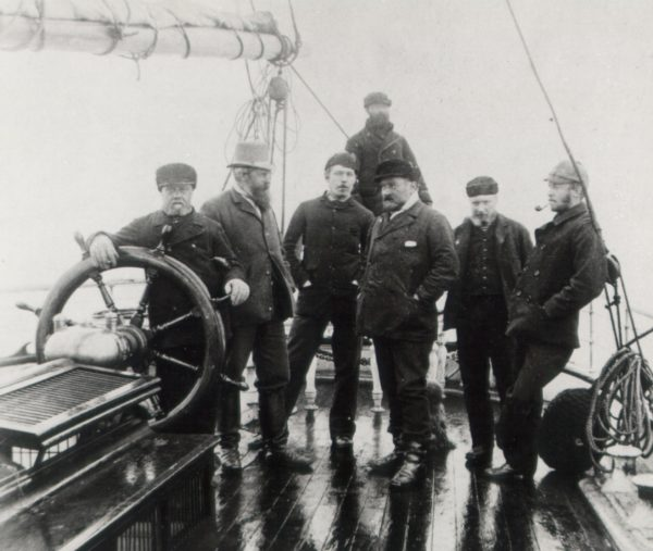 Arthur Conan Doyle stands in the middle of the crew of the Eira, an arctic exploration ship with several other men